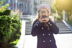 Little funny girl wearing glasses with pleasure - eating a chocolate donut royalty free stock image