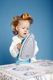 Little funny housewife with iron Stock Photos