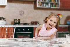 Little funny kid girl in pink dress playing, smearing hands and face with flour in light kitchen at table. Child