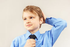 Little funny kid straighten tie over bright blue shirt Royalty Free Stock Images