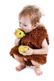 Little funny Neanderthal boy in a suit with dirty face eating an apple. Little funny Neanderthal boy in a suit with a dirty face eating an apple. Humorous Royalty Free Stock Images