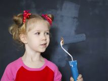 Little smiling girl paint the wall with magnetic paint. Little funny smiling girl paint the wall with magnetic paint Royalty Free Stock Photo