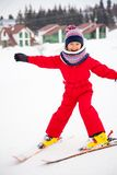 Little smiling girl in red overall training skiing royalty free stock photos