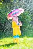 Little funny toddler with umbrella playing in rain Stock Photography