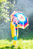Little funny toddler with umbrella playing in rain Royalty Free Stock Photography