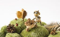 Little garden helper with handcart harvesting acorns autumn season background royalty free stock photos