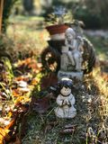 Little garden sculptures. Close-up on the ground with withered leaves Stock Photography