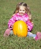 Little gardener girl with pumpkin at green grass Royalty Free Stock Photos