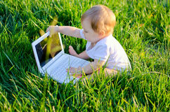Little genius. Baby girl sitting on the green grass with laptop stock photos