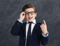 Little genius boy having idea. Little genius. Small boy in suit having great idea, point up with his finger, studio background, copy space royalty free stock photography