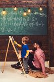 Little genius learning math. Teacher or father helping kid to solve equation on chalkboard. Bearded guy in pink shirt. Little genius learning math. Teacher or stock photography