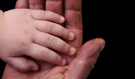 Little gentle hand of the child in the rough worker`s hand Royalty Free Stock Photography