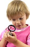 Little geologist. Girl with magnifying glass studying a rock Royalty Free Stock Photography
