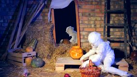 Little Ghost Picking Up Apples At Halloween stock video footage