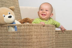 Little gift 13. A very cute 8-9 months old baby is playing with teddy bears in a basket. This is a full series of 14 photos, take a look at them all before you Stock Photo