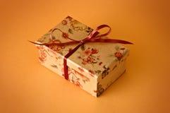 Little gift. Isolated on orange background Royalty Free Stock Images