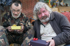 Little gift. Frustrated homeless men with little christmas gift Stock Photo