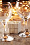 Little gift. And wine glass on holiday table. Focus on gift, shallow DOF stock photos