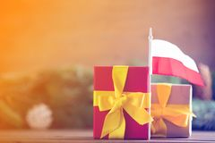 Little gifts box with Poland flag. And pine cones and branches on background. Image in Christmas holiday decoration style Royalty Free Stock Images