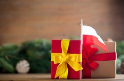 Little gifts box with Poland flag. And pine cones and branches on background. Image in Christmas holiday decoration style Royalty Free Stock Photo