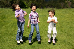 Little Giggling Girls. 3 little giggling dark haired girls jumping in the grass Royalty Free Stock Photography