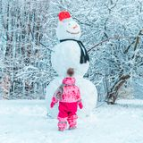 Little gild kid in pink winter clothes looking at big snowman royalty free stock images
