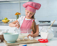Little gilr mixing ingredients for a dough Stock Images