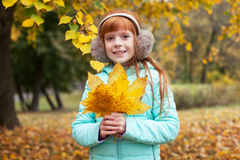 Little ginger girl in autumn park Royalty Free Stock Image