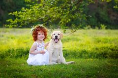 LIttle ginger girl and big dog bestfriend on nature background.  Royalty Free Stock Image