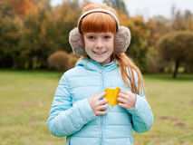Little ginger girl holding a heart shaped leaf Stock Photos