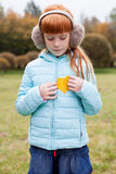Little ginger girl holding a heart shaped leaf Royalty Free Stock Images