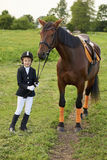 Little gir jockeyl lead horse by its reins across country in professional outfit. Pretty little gir jockeyl lead horse by its reins across country in Stock Images