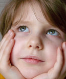 Little girl 1. Little thoughtful girl face in hands closeup Stock Images