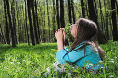 Little girl. Sitting on a grass in the woods Royalty Free Stock Photography
