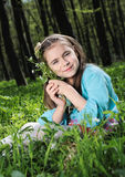 Little girl. Sitting on a grass in the woods Royalty Free Stock Images