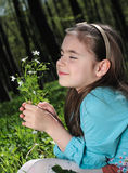 Little girl. Sitting on a grass in the woods Royalty Free Stock Photo