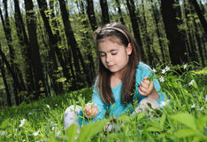 Little girl. Sitting on a grass in the woods Stock Image