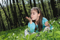 Little girl. Sitting on a grass in the woods Stock Photography