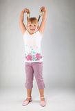 Little girl. Girl shows her plaits . Gray background Royalty Free Stock Photo