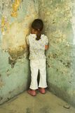Little Girl. Girl standing face foward against an old wall Royalty Free Stock Photography