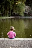 Little Girl. A little girl is sitting on the river bank by herself, contemplating water with a doll under her arm. She's dreaming of sweet things as the water Stock Photo