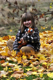 Little girl. Sitting in the fallen autumn leaves Stock Images