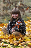 Little girl. Sitting in the fallen autumn leaves Royalty Free Stock Images