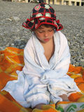 Little girl. Wrapped in towel siting on pebble beach stock photo