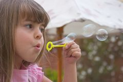 Little girl. A cute young girl plays with bubbles stock photo