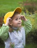 Little girl. Baby with yellow cap in autumn Royalty Free Stock Image