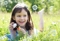 Little girl. Little beautiful happy girl blowing soap bubbles Royalty Free Stock Photos