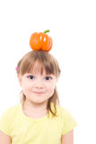 Little girl. The portrait of a cute little girl holding an orange pepper on her head Royalty Free Stock Image
