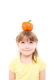 Little girl. The portrait of a cute little girl holding an orange pepper on her head Stock Images