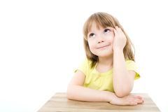Little girl. The portrait of a clever little girl sitting at the table Stock Photo